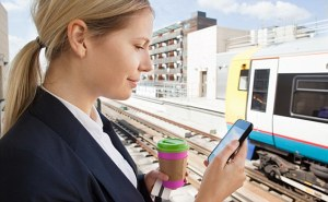 Businesswoman with coffee and smart phone in train station